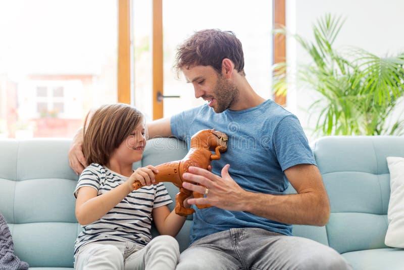 Παιχνίδι πατέρων με το γιο του στον καναπέ στοκ εικόνα με δικαίωμα ελεύθερης χρήσης