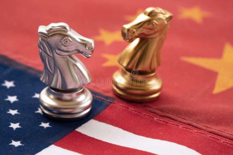 Παιχνίδι σκακιού, δύο ιππότες πρόσωπο με πρόσωπο στην Κίνα και αμερικανικές εθνικές σημαίες Έννοια εμπορικών πολέμων Σύγκρουση με στοκ φωτογραφίες