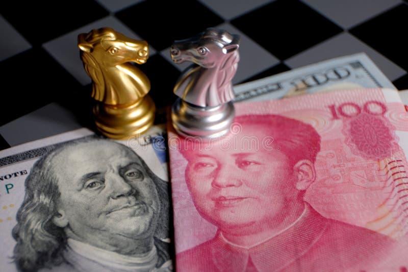 Παιχνίδι σκακιού, δύο ιππότες πρόσωπο με πρόσωπο στο κινεζικό yuan και υπόβαθρο αμερικανικών δολαρίων Έννοια εμπορικών τρόπων Σύγ στοκ φωτογραφία