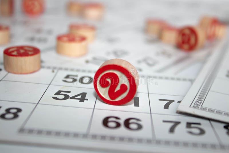 Παιχνίδι Bingo ή λότο Ξύλινα βυτία του λότο στις κάρτες Κάρτες και τσιπ για το bingo παιχνιδιού σε έναν άσπρο πίνακα στοκ φωτογραφία με δικαίωμα ελεύθερης χρήσης