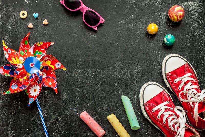 Παιχνίδια και κόκκινα πάνινα παπούτσια στο μαύρο πίνακα κιμωλίας - παιδική ηλικία στοκ εικόνα