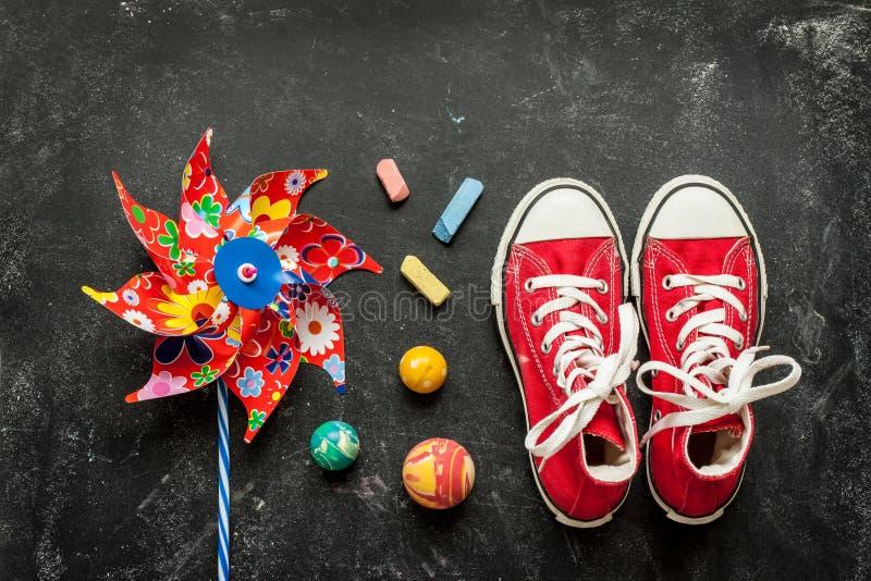 Παιχνίδια και κόκκινα πάνινα παπούτσια στο μαύρο πίνακα κιμωλίας - παιδική ηλικία στοκ φωτογραφίες με δικαίωμα ελεύθερης χρήσης