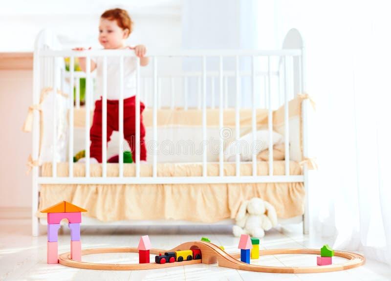 Παιχνίδια στο πάτωμα στην ηλιόλουστη κρεβατοκάμαρα με το μωρό νηπίων στο παχνί στο υπόβαθρο στοκ εικόνες