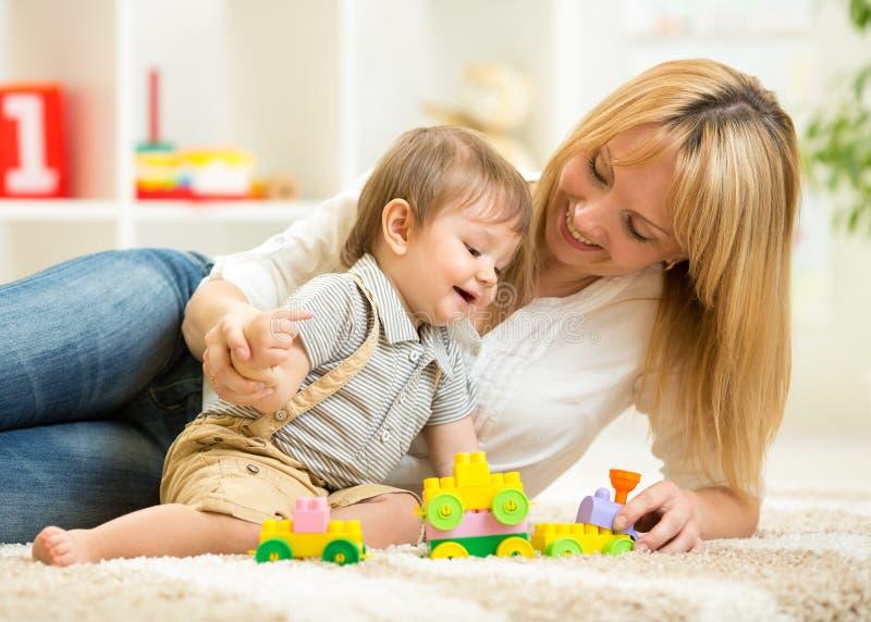 Παιχνίδια φραγμών παιχνιδιού Mom και γιων στο σπίτι στοκ εικόνες