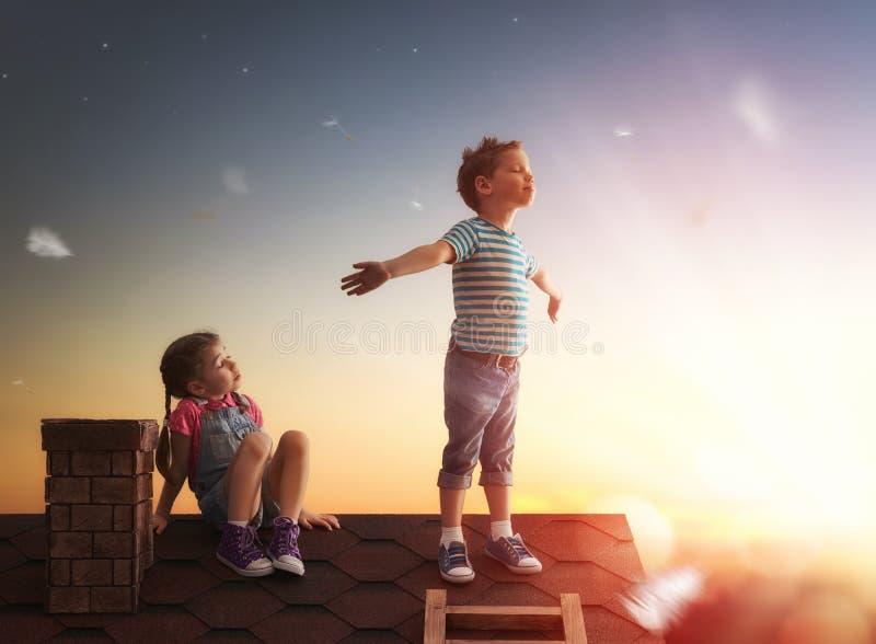 Παιχνίδι αγοριών και κοριτσιών στη στέγη στοκ εικόνα με δικαίωμα ελεύθερης χρήσης