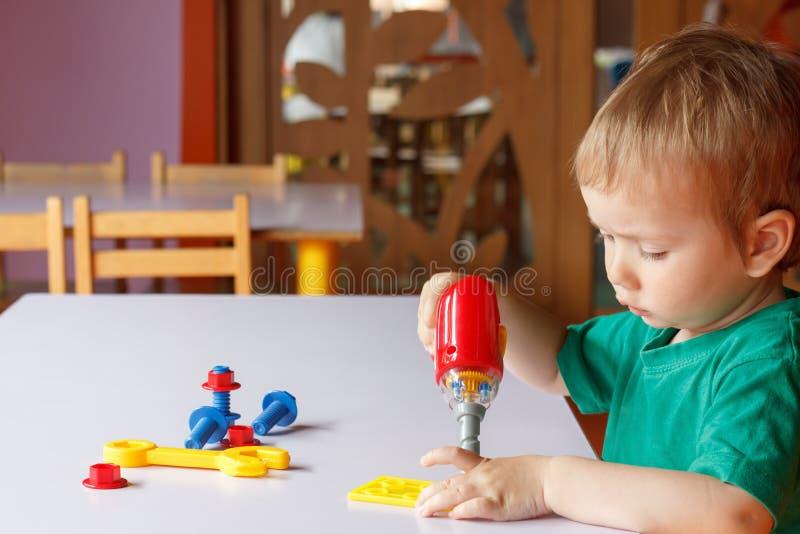 Παιχνίδι αγοριών παιδιών παιδιών με τα παιχνίδια στοκ εικόνα