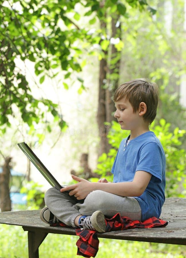 Παιχνίδι αγοριών στον υπολογιστή (lap-top) στοκ εικόνες