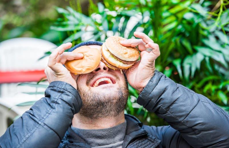 Παιχνίδι ατόμων με τα τρόφιμά του - που τοποθετούν τα χάμπουργκέρ του στο πρόσωπό του στοκ εικόνα