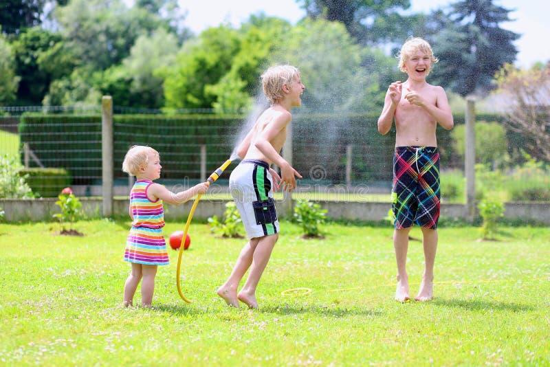 Παιχνίδι αδελφών και αδελφών με τη μάνικα νερού στον κήπο στοκ φωτογραφίες με δικαίωμα ελεύθερης χρήσης