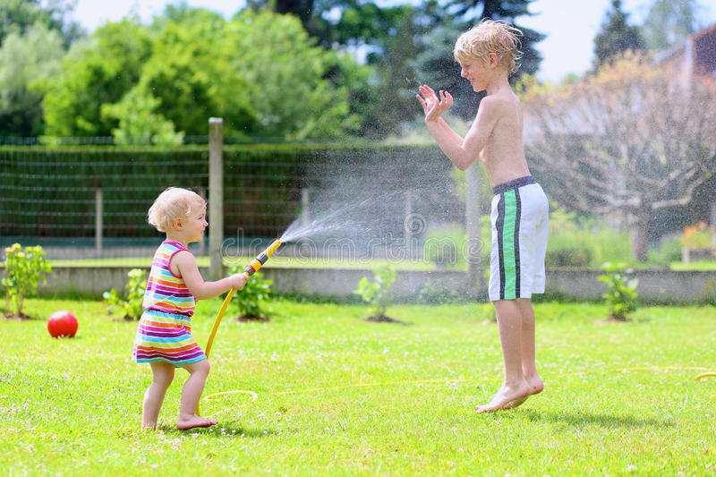 Παιχνίδι αδελφών και αδελφών με τη μάνικα νερού στον κήπο στοκ εικόνες