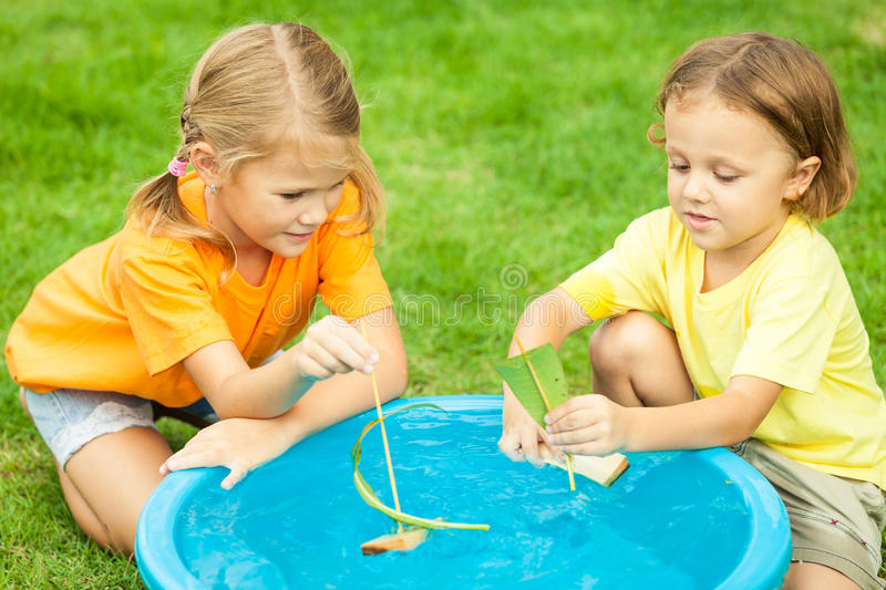 Παιχνίδι αδελφών και αδελφών με το νερό κοντά σε ένα σπίτι στο Tj ημέρας στοκ εικόνες