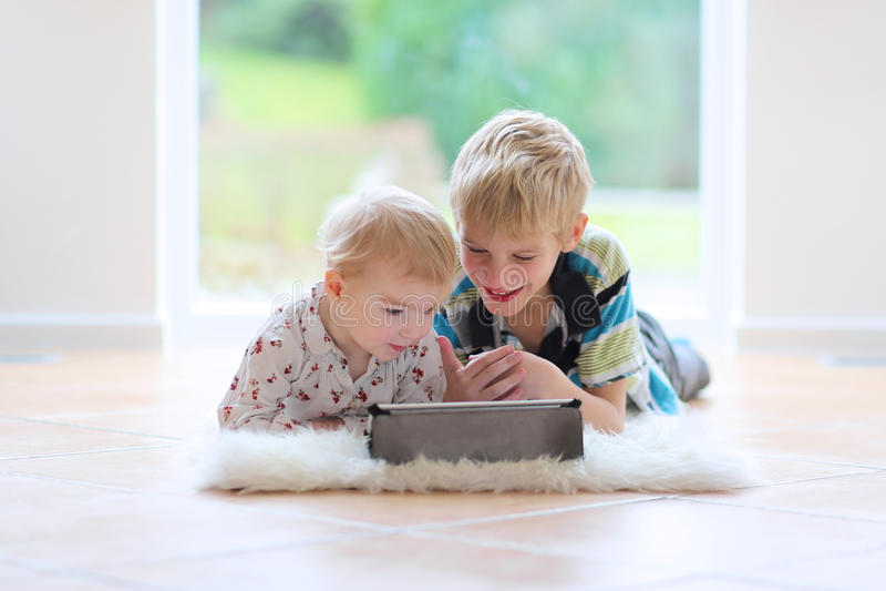 Παιχνίδι αδελφών και αδελφών με το PC ταμπλετών στο εσωτερικό στοκ εικόνα με δικαίωμα ελεύθερης χρήσης