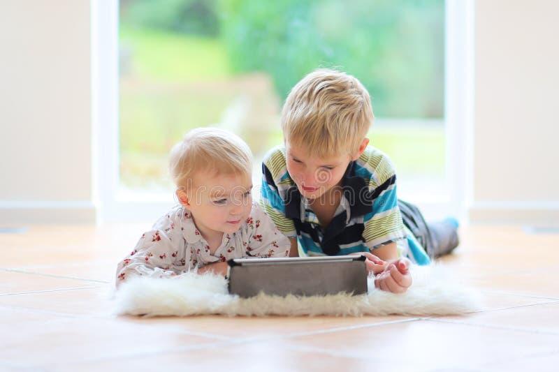 Παιχνίδι αδελφών και αδελφών με το PC ταμπλετών στοκ φωτογραφία