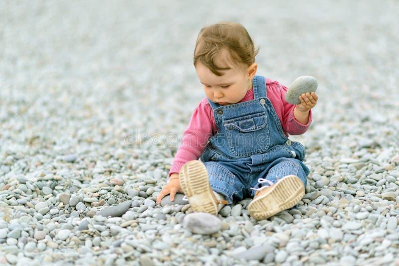 Παιχνίδι κοριτσάκι με τα χαλίκια στην παραλία στοκ εικόνες