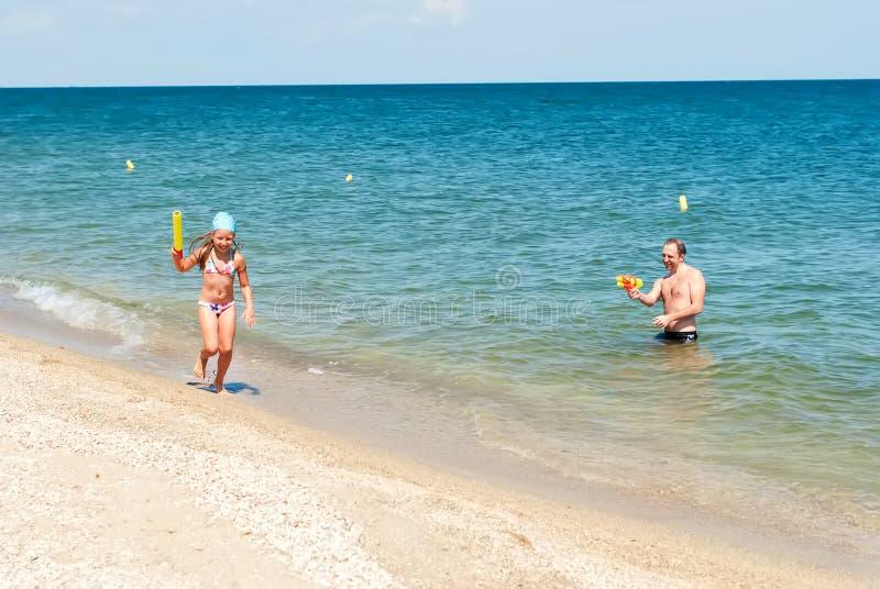 Παιχνίδι κοριτσιών με τον μπαμπά στην παραλία στοκ φωτογραφίες