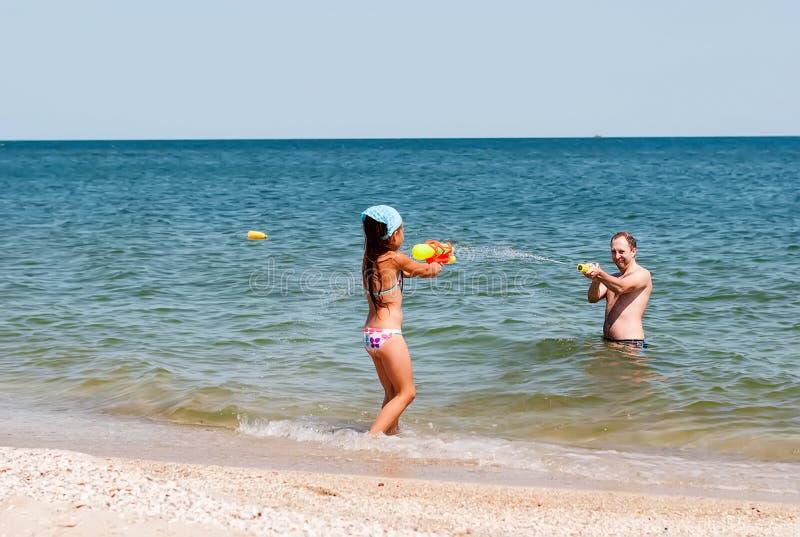 Παιχνίδι κοριτσιών με τον μπαμπά στην παραλία στοκ φωτογραφίες με δικαίωμα ελεύθερης χρήσης