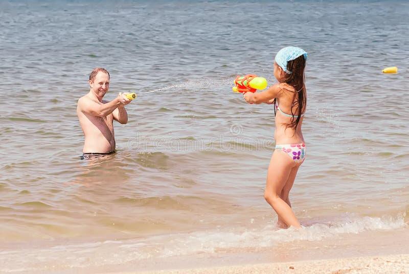 Παιχνίδι κοριτσιών με τον μπαμπά στην παραλία στοκ εικόνες