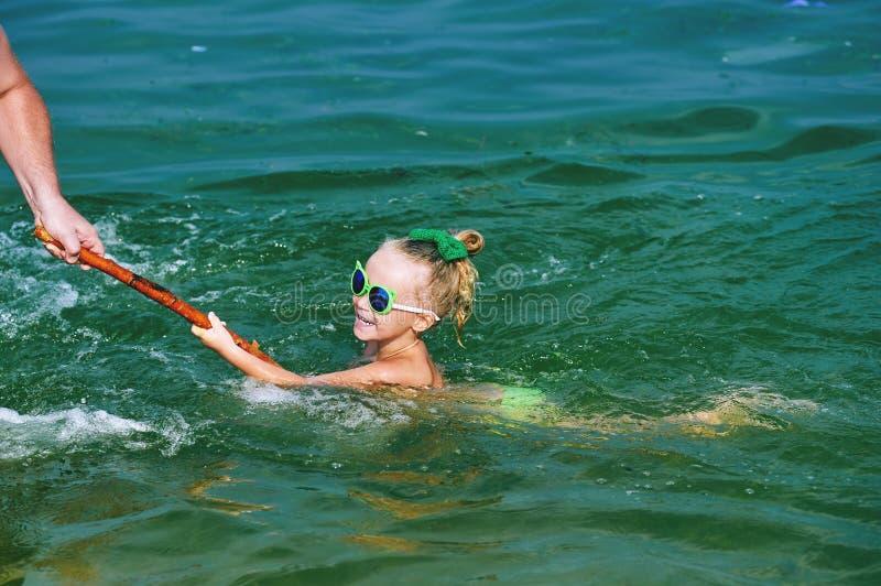 Παιχνίδι κοριτσιών στη θάλασσα, που μαθαίνει να κολυμπά στοκ εικόνα με δικαίωμα ελεύθερης χρήσης