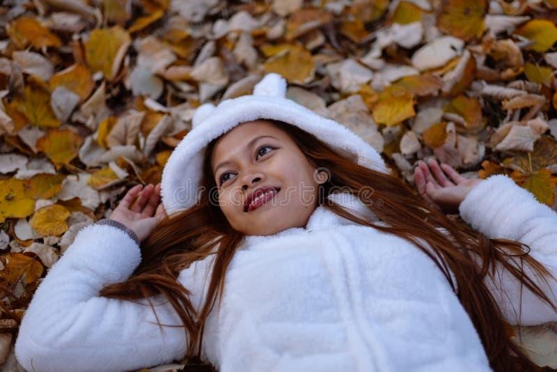 Παιχνίδι κοριτσιών φθινοπώρου στο πάρκο πόλεων Πορτρέτο μιας γυναίκας φθινοπώρου που βρίσκεται πέρα από τα φύλλα και που χαμογελά στοκ φωτογραφία