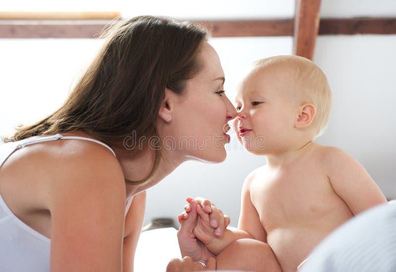 Παιχνίδι μητέρων και μωρών στο κρεβάτι στοκ φωτογραφία