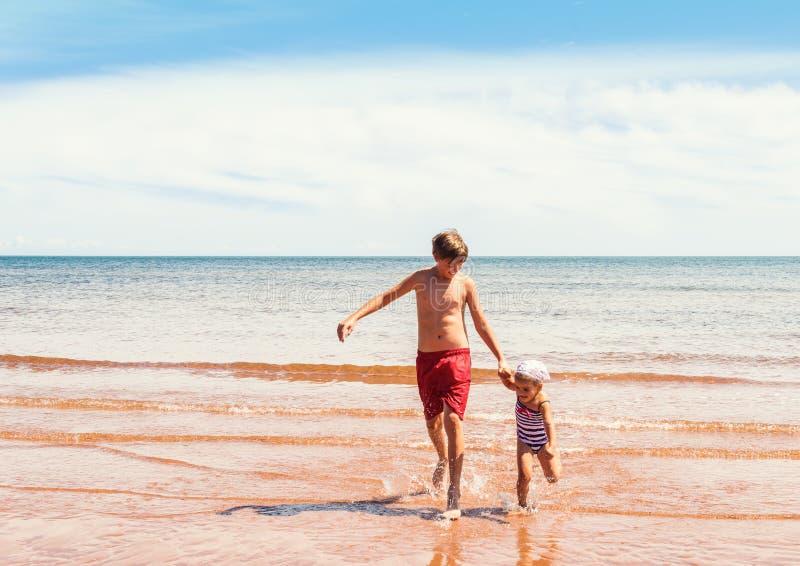 Παιχνίδι μικρών κοριτσιών και αγοριών στην παραλία στοκ εικόνα με δικαίωμα ελεύθερης χρήσης