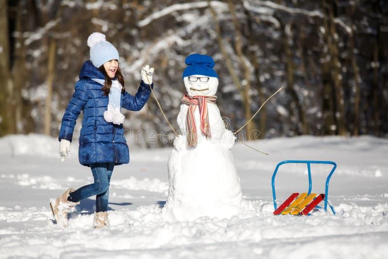 Παιχνίδι μικρών κοριτσιών με έναν χιονάνθρωπο στοκ εικόνες