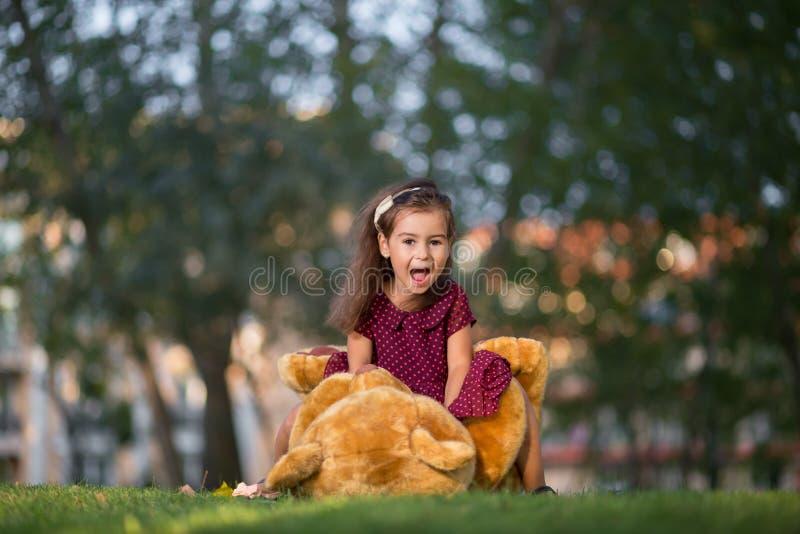 Παιχνίδι μικρών κοριτσιών με μια teddy αρκούδα στο πάρκο στοκ εικόνα με δικαίωμα ελεύθερης χρήσης