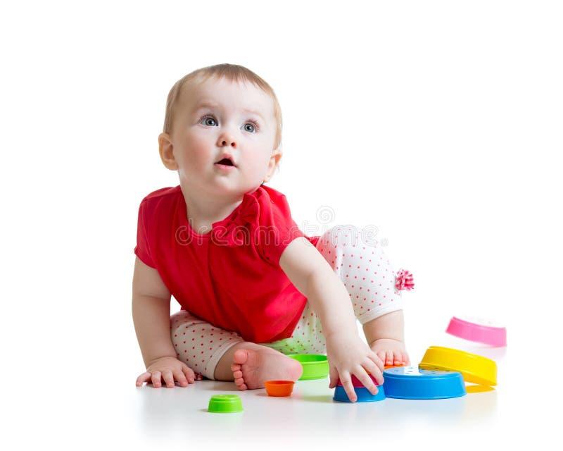 Παιχνίδι μικρών κοριτσιών με τα παιχνίδια που απομονώνονται στοκ φωτογραφία