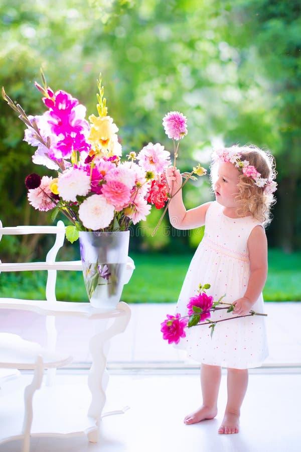 Παιχνίδι μικρών κοριτσιών με τα φρέσκα λουλούδια στοκ φωτογραφία με δικαίωμα ελεύθερης χρήσης