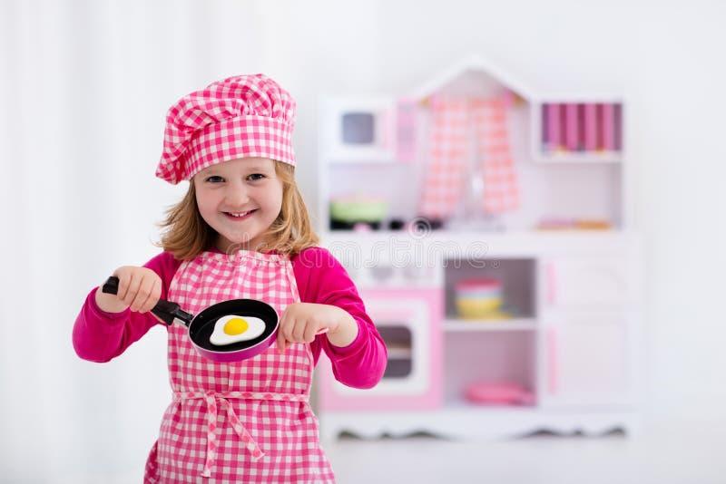 Παιχνίδι μικρών κοριτσιών με την κουζίνα παιχνιδιών στοκ φωτογραφίες