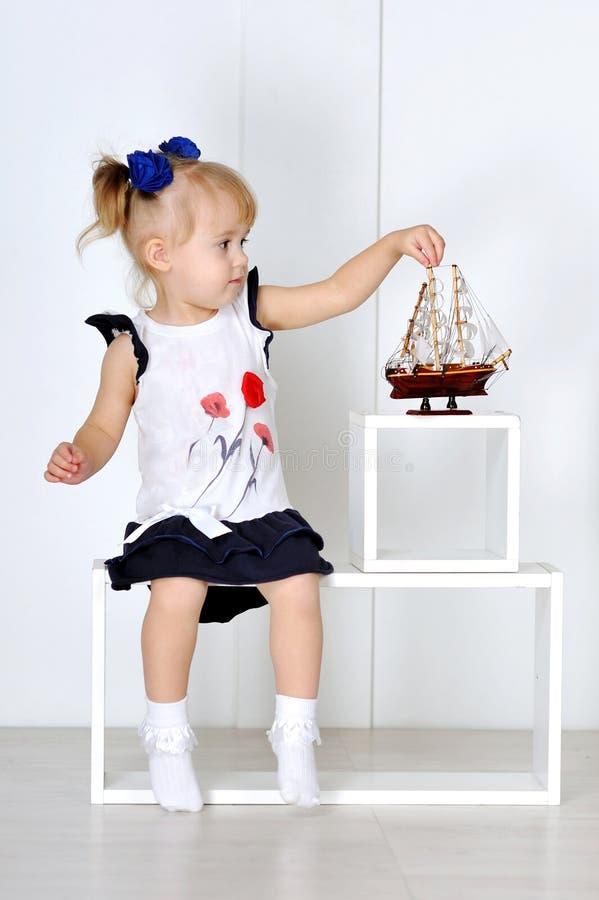 Παιχνίδι μικρών κοριτσιών με τη βάρκα παιχνιδιών στο στούντιο στοκ εικόνα με δικαίωμα ελεύθερης χρήσης