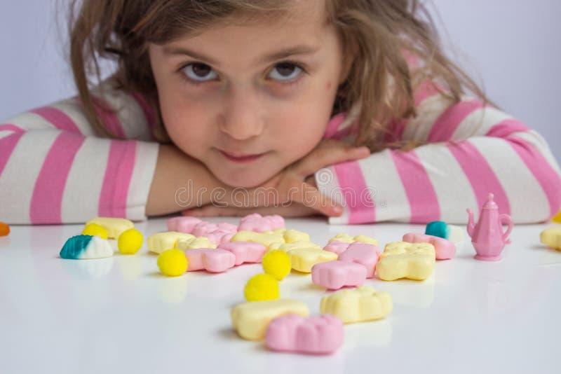 Παιχνίδι μικρών κοριτσιών με τις καραμέλες στοκ εικόνα