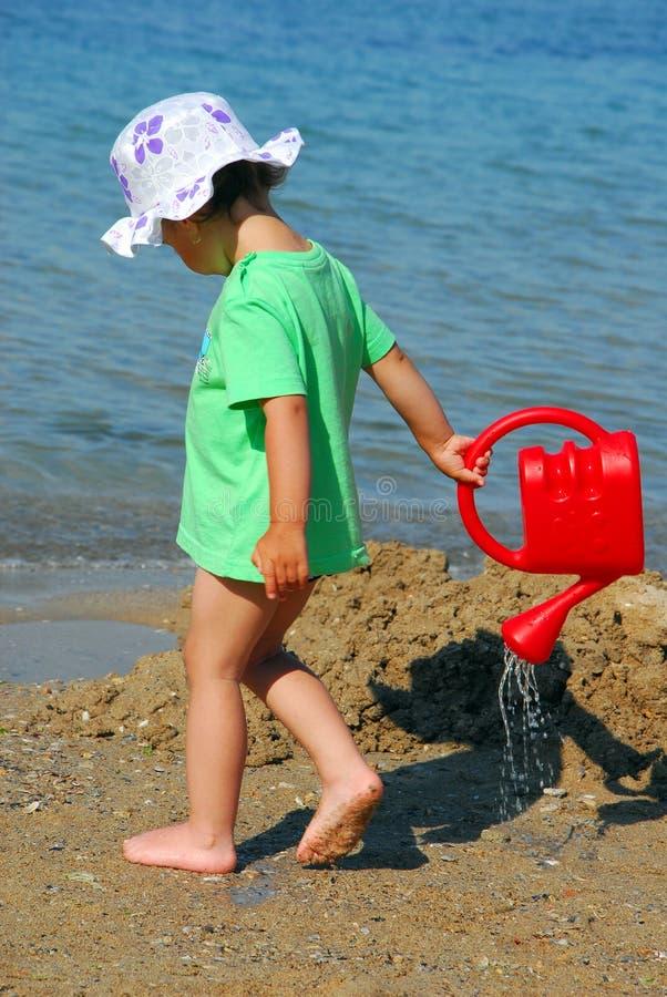 Παιχνίδι μικρών κοριτσιών με τον ψεκαστήρα της στην παραλία στοκ εικόνα με δικαίωμα ελεύθερης χρήσης
