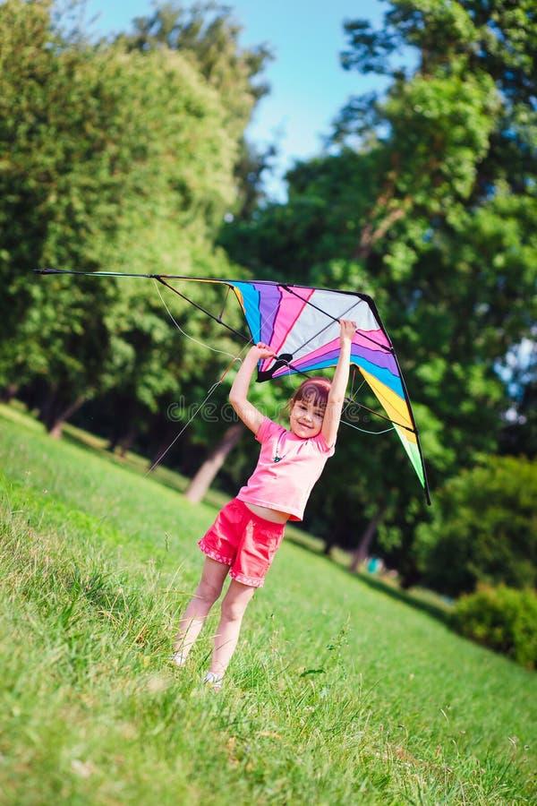 Παιχνίδι μικρών κοριτσιών με το χρωματισμένο ικτίνο στο πάρκο στοκ φωτογραφία με δικαίωμα ελεύθερης χρήσης