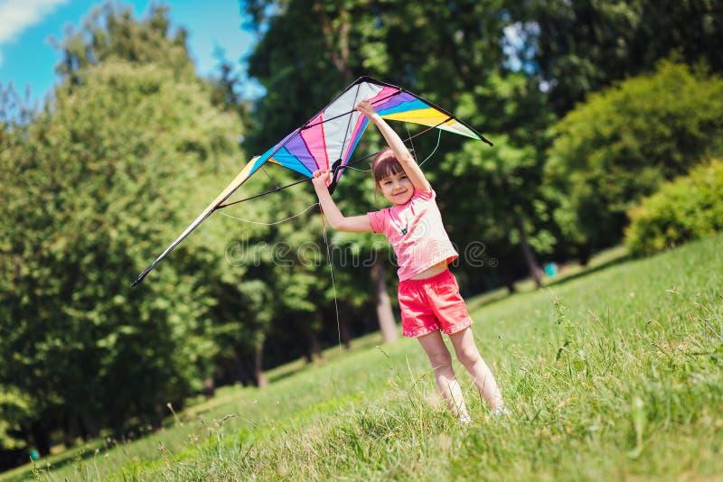 Παιχνίδι μικρών κοριτσιών με το χρωματισμένο ικτίνο στο πάρκο στοκ εικόνα