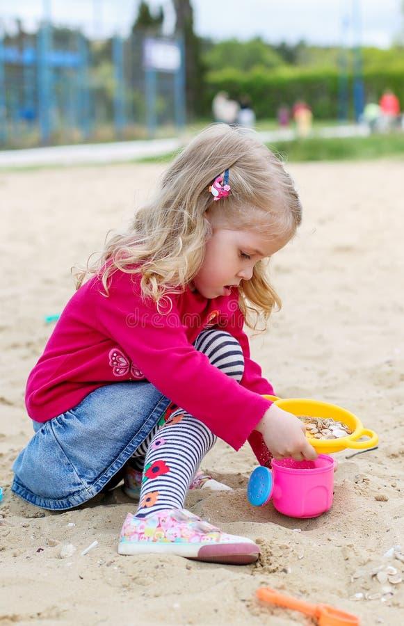 Παιχνίδι μικρών κοριτσιών στα παιχνίδια άμμου στοκ εικόνα