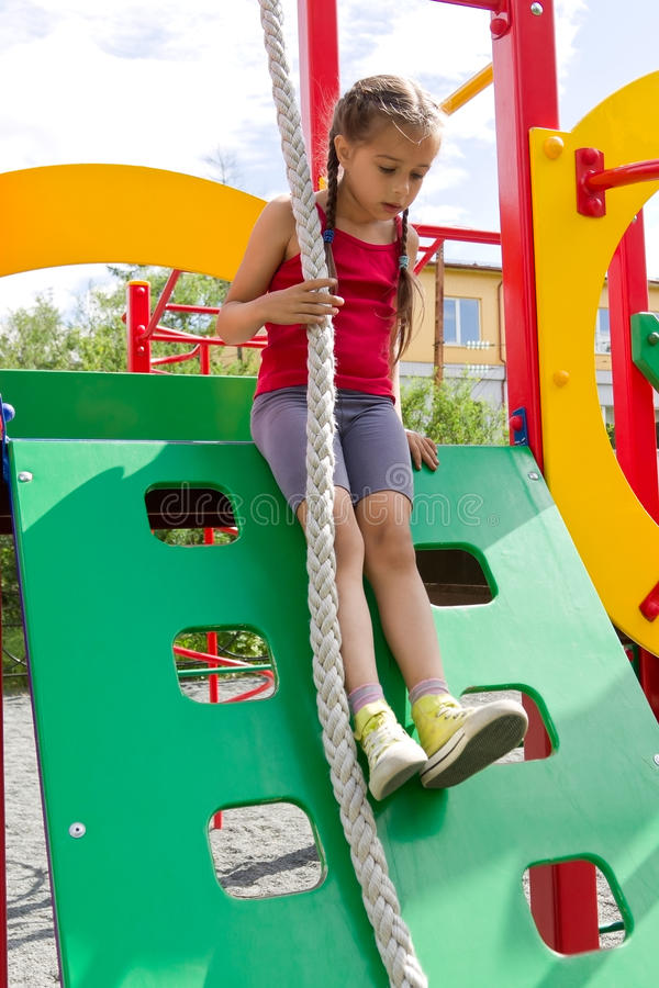 Παιχνίδι μικρών κοριτσιών στην παιδική χαρά, που γλιστρά κάτω από τον ξύλινο τοίχο στοκ εικόνα