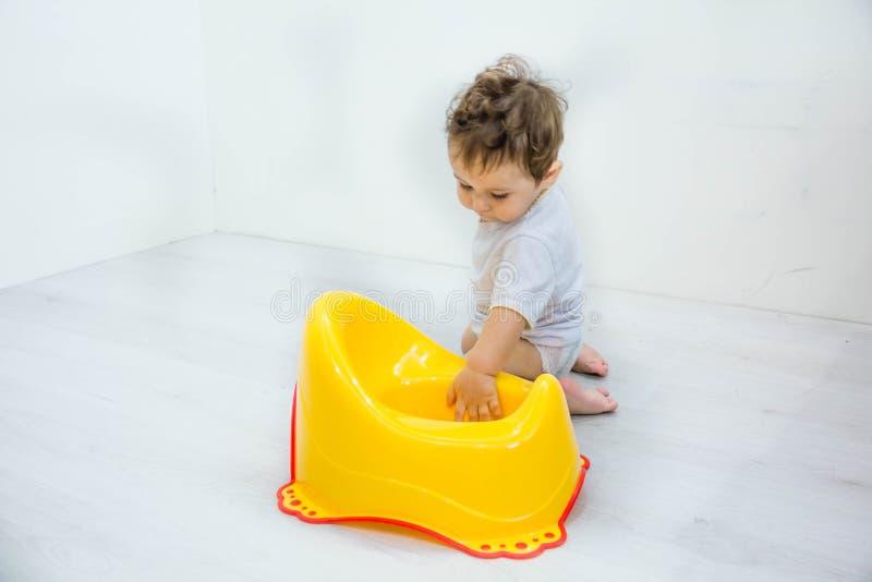 Παιχνίδι μικρών παιδιών αγοράκι παιδιών νηπίων με το ασήμαντο δοχείο σκαμνιών τουαλετών σε ένα άσπρο υπόβαθρο στοκ εικόνες με δικαίωμα ελεύθερης χρήσης