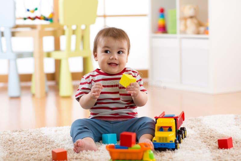 Παιχνίδι μικρών παιδιών αγοριών παιδιών με το αυτοκίνητο παιχνιδιών στο εσωτερικό στοκ εικόνες