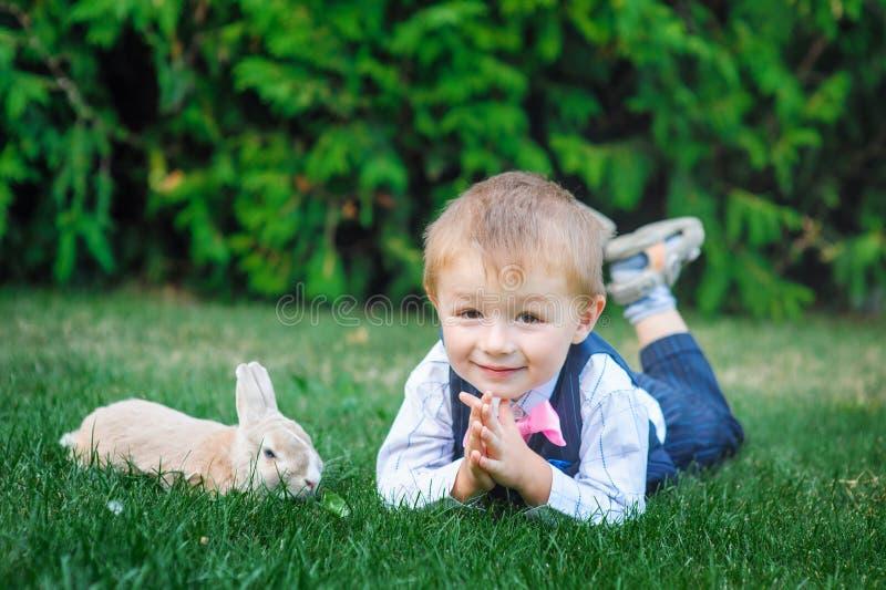 Παιχνίδι μικρών παιδιών με το κουνέλι στην πράσινη χλόη στοκ εικόνα