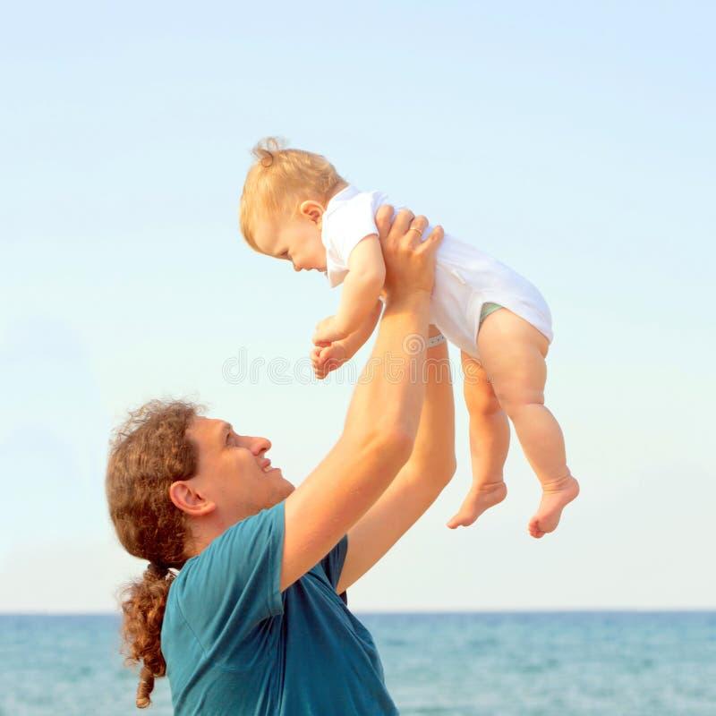 Παιχνίδι μπαμπάδων με το μωρό στην παραλία στοκ εικόνες με δικαίωμα ελεύθερης χρήσης