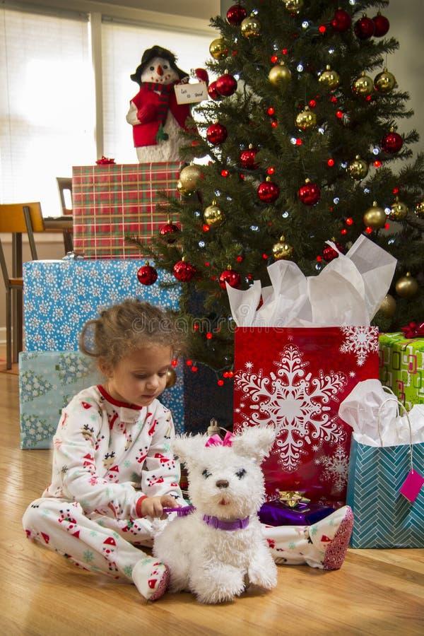 Παιχνίδι νέων κοριτσιών με το σκυλί παιχνιδιών μπροστά από το χριστουγεννιάτικο δέντρο στοκ εικόνα με δικαίωμα ελεύθερης χρήσης