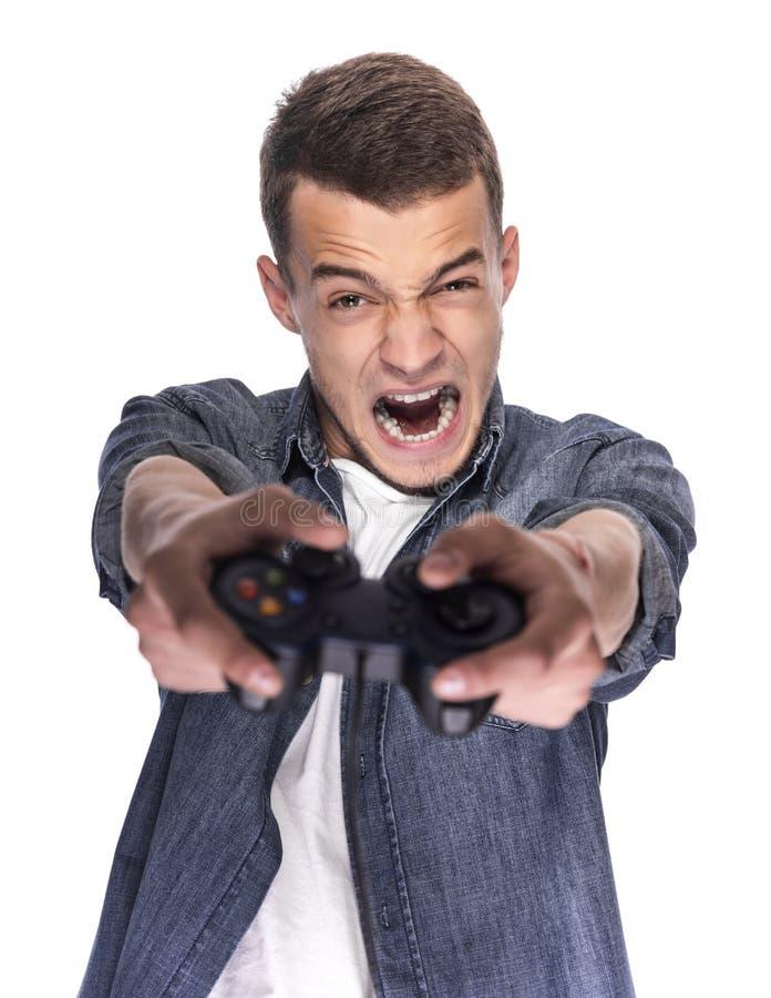 Παιχνίδι νεαρών άνδρων στην κονσόλα ή τον υπολογιστή στοκ φωτογραφία