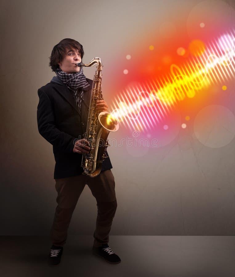 Παιχνίδι νεαρών άνδρων στο saxophone με τα ζωηρόχρωμα υγιή κύματα στοκ εικόνες