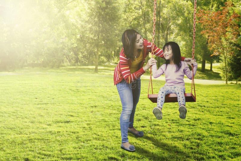 Παιχνίδι παιδιών και μητέρων στην ταλάντευση στοκ φωτογραφία