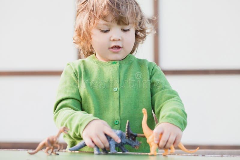 Παιχνίδι παιδιών μικρών παιδιών με έναν δεινόσαυρο παιχνιδιών στοκ φωτογραφία
