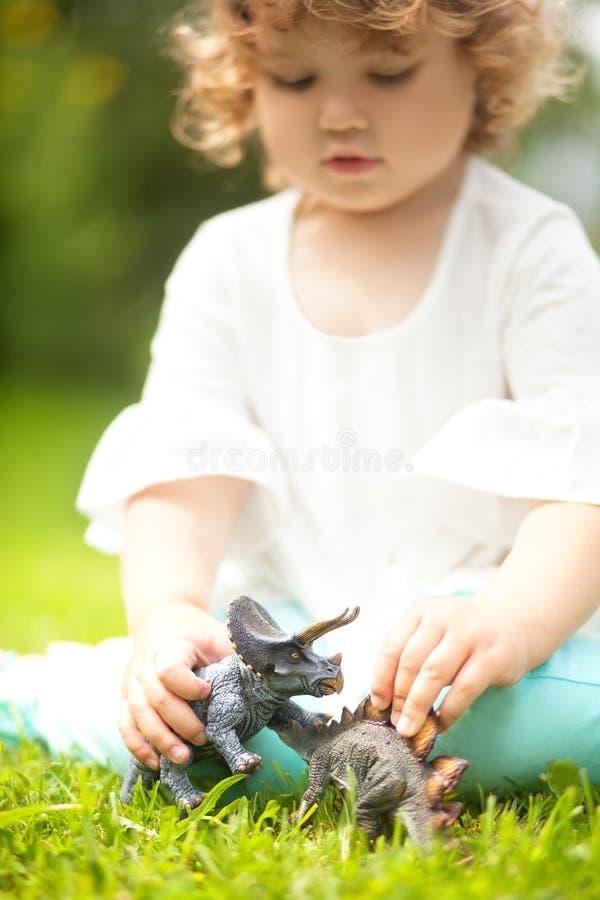 Παιχνίδι παιδιών μικρών παιδιών με έναν δεινόσαυρο παιχνιδιών στοκ φωτογραφίες με δικαίωμα ελεύθερης χρήσης