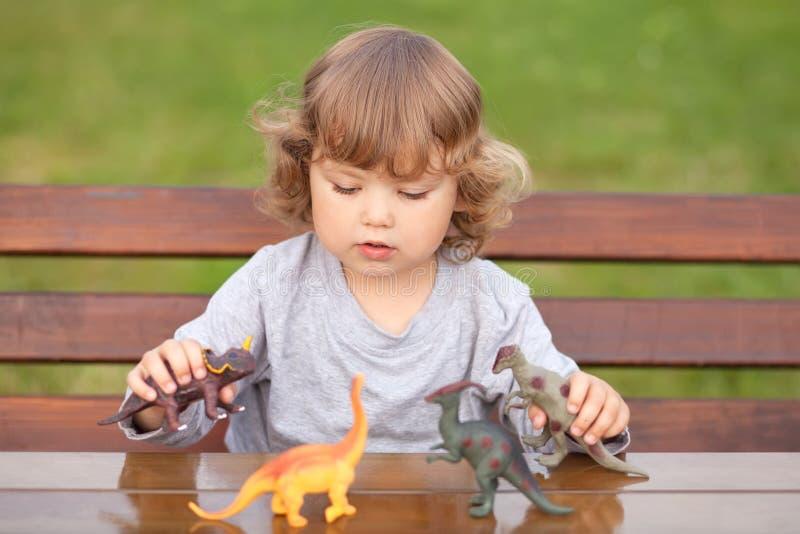 Παιχνίδι παιδιών μικρών παιδιών με έναν δεινόσαυρο παιχνιδιών στοκ εικόνα