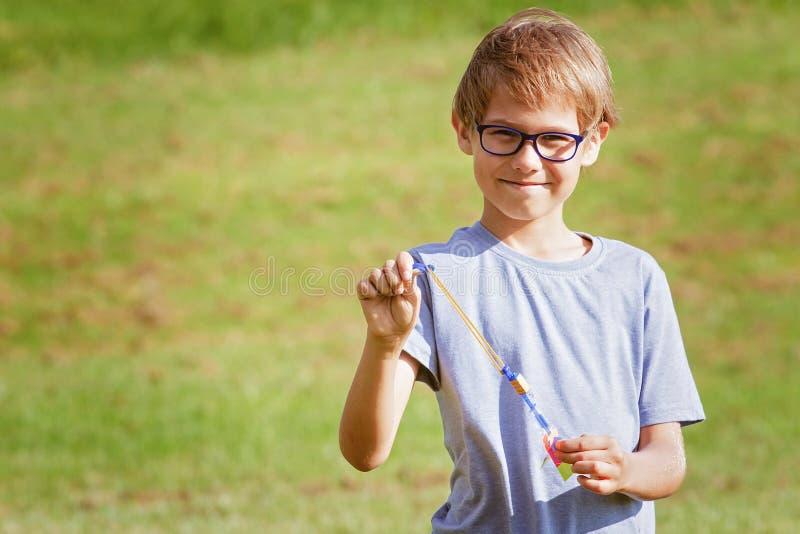 Παιχνίδι παιδιών υπαίθρια σε ένα πάρκο με το ελαστικό παιχνίδι πυραύλων ελικοπτέρων βελών στοκ εικόνα