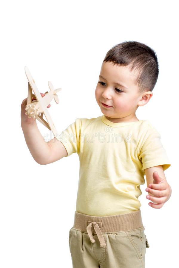 Παιχνίδι παιδιών χαμόγελου με το ξύλινο παιχνίδι αεροπλάνων στοκ φωτογραφία με δικαίωμα ελεύθερης χρήσης